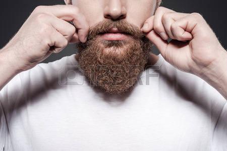 32264153-彼自身のスタイルを作ること。灰色の背景に対して立っている間彼の口ひげを調整あごひげを生やした若者のクローズ-アップ