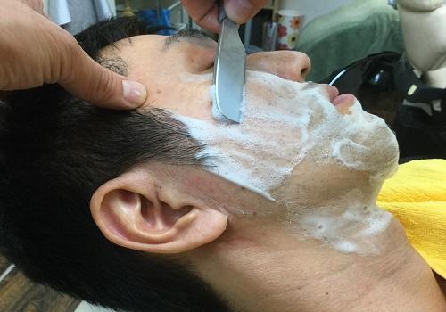 日本刀で男性の顔そりをしている画像