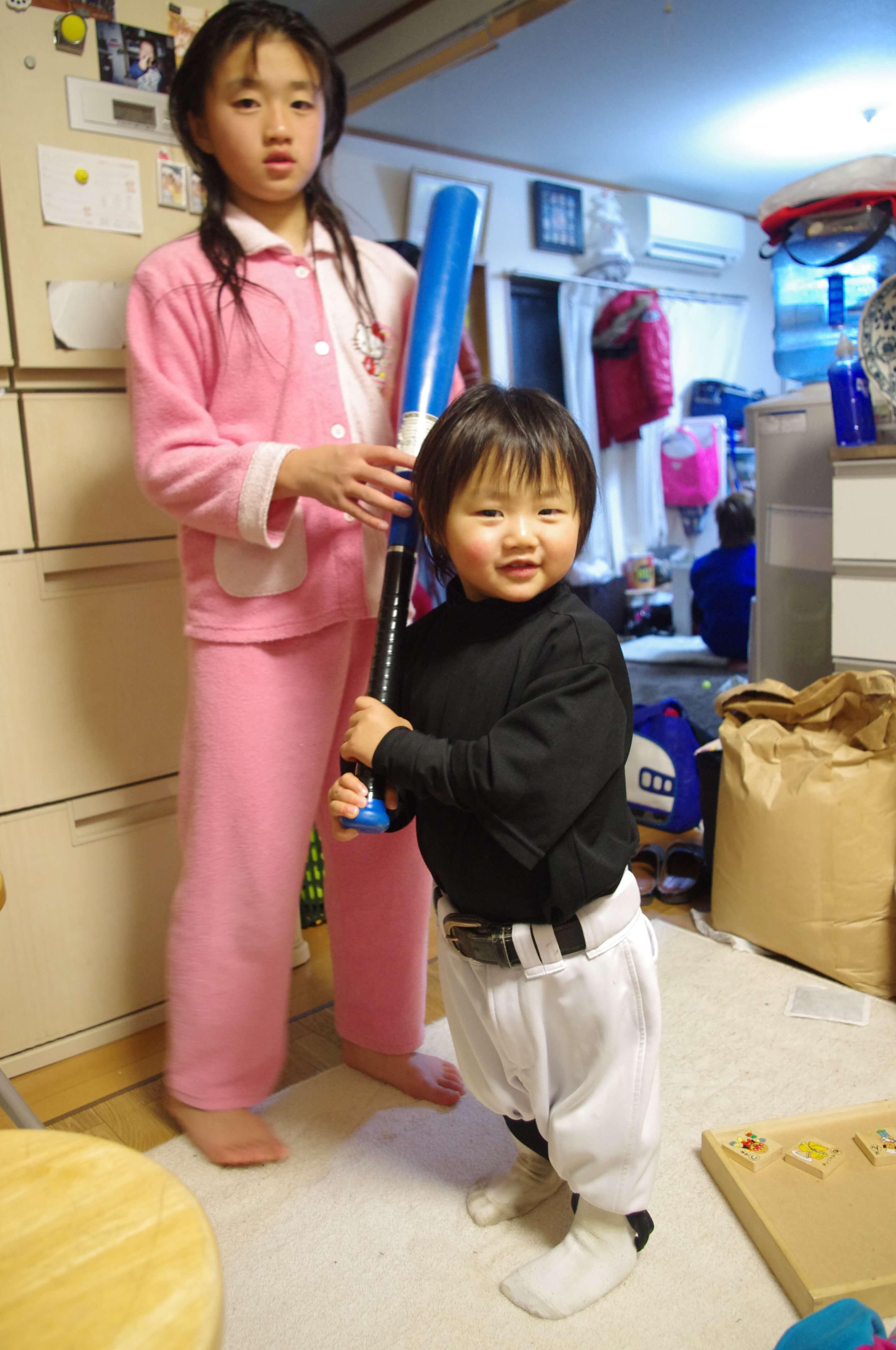 野球のユニフォームを着ておもちゃのバットを持つ幼児