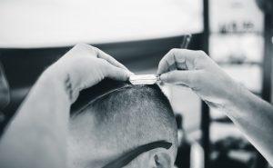男性の髪にカミソリを当てている画像