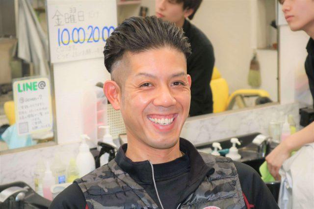 理容室で笑う男性の画像