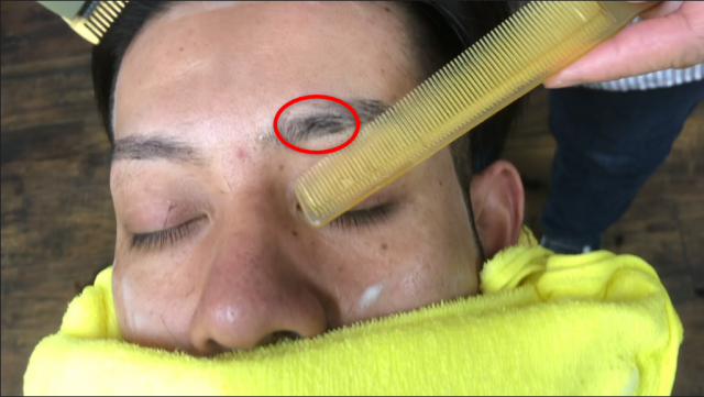 男性が眉毛をカットしている画像